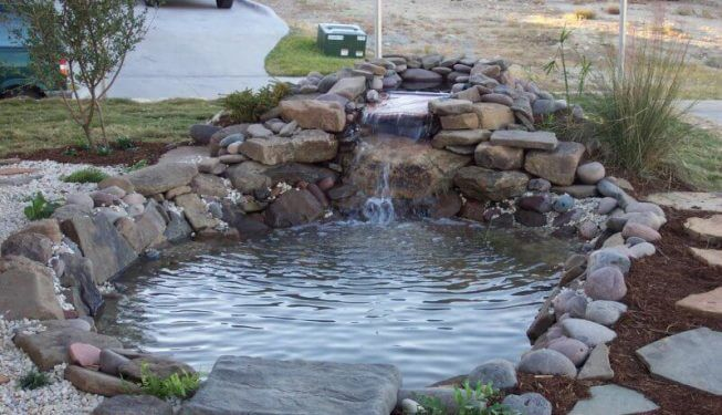 Serene pond water feature near driveway